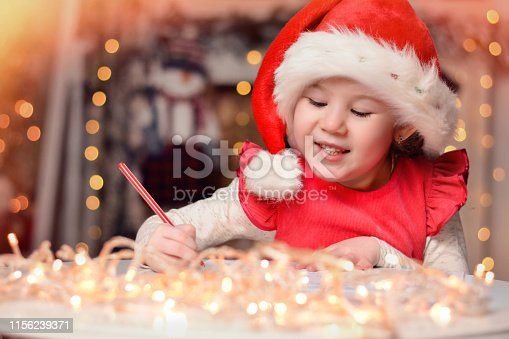 1062609644istockphoto Cute little child girl writes the letter to Santa Claus near Christmas tree indoors.Merry Christmas and Happy Holidays! 1156239371