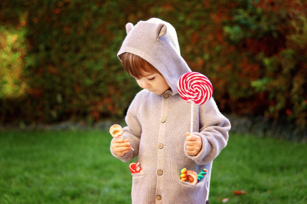 Cute little child in funny jacket with ears holding sweet lollipop candies choosing one. Sweet tooth. Happy childhood. Cute little child in funny jacket with ears holding sweet lollipop candies choosing one. Sweet tooth. Happy childhood. hot pockets stock pictures, royalty-free photos & images