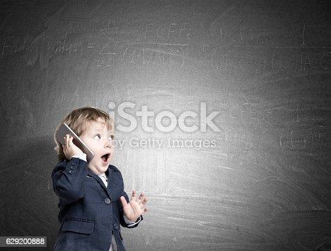 istock Cute little child on the phone near a chalkboard 629200888