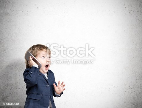 istock Cute little child on the phone near a concrete wall 629606348