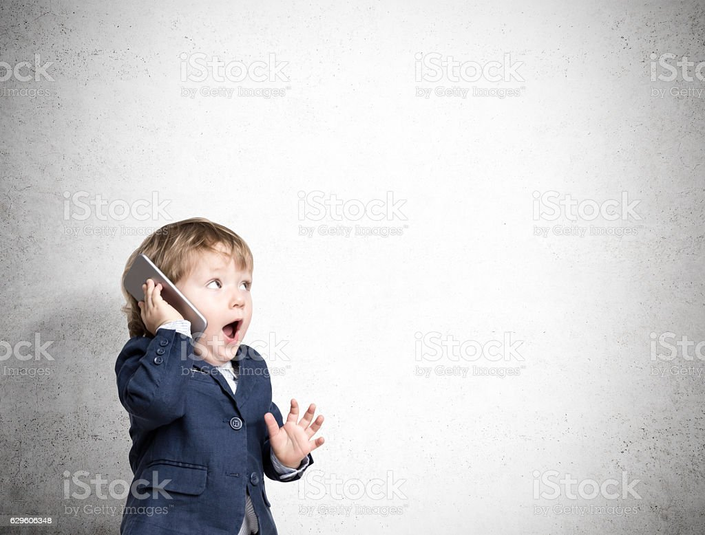 Cute little child on the phone near a concrete wall stock photo
