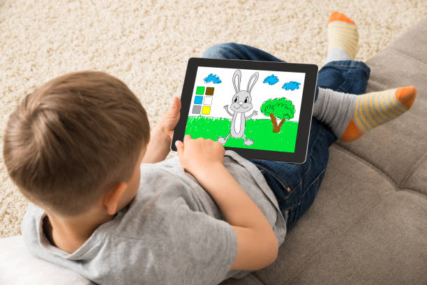 Cute Little Child Playing Game On Digital Tablet High Angle View Of Cute Little Child Playing Game On Digital Tablet digital native stock pictures, royalty-free photos & images