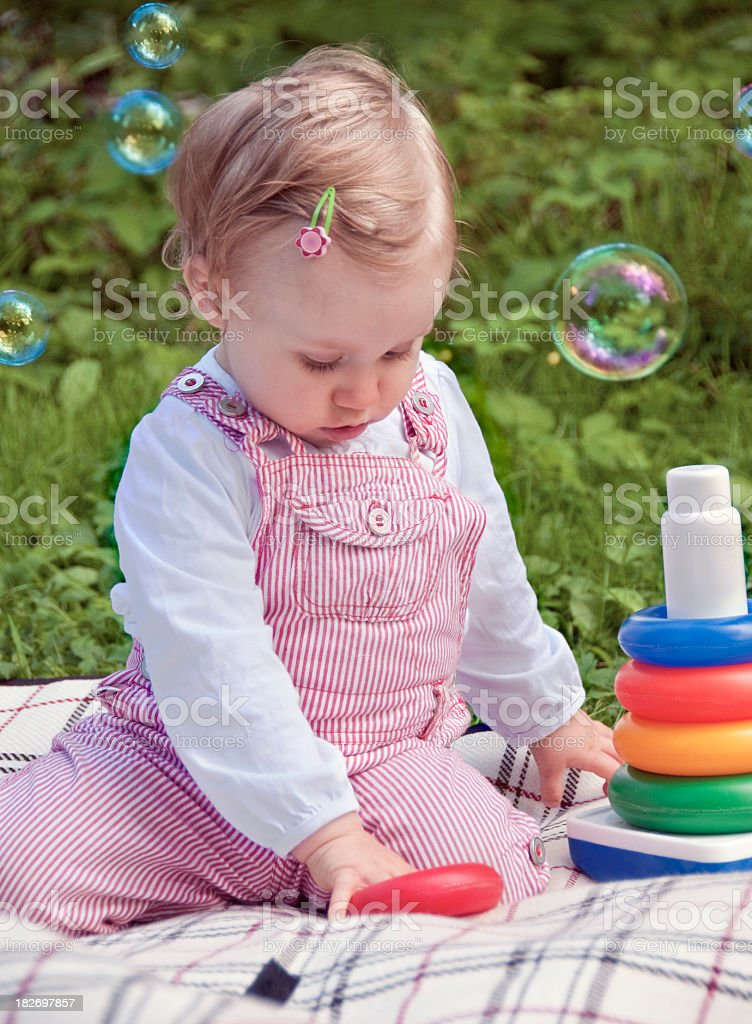 Cute little child toddler playing soap bubbles blanket green garden royalty-free stock photo