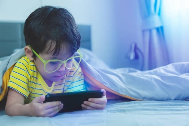 Cute little child watch movie on smartphone at bed. Dangers of blue light can damage eyes. Handsome little boy can be age related macular degeneration from blue light, wear eyeglasses since childhood stock photo