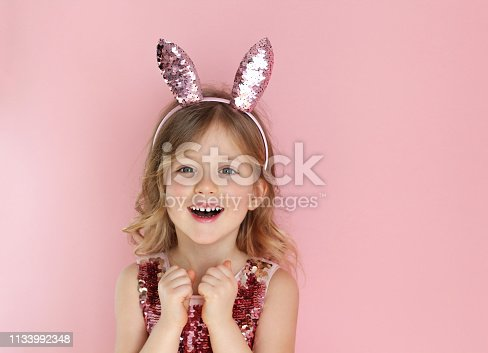 Cute little child wearing sparkling bunny ears on Easter day on pink background. Easter girl portrait, funny emotions, surprise. Copyspace for text.