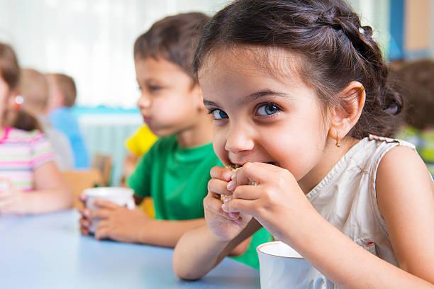 cute little children drinking milk - snack stockfoto's en -beelden