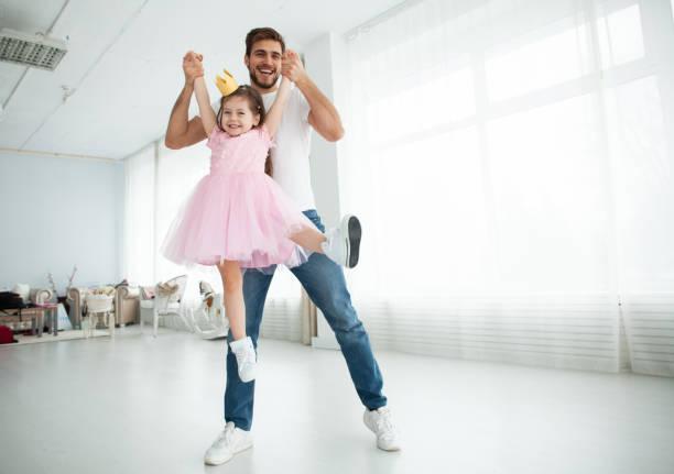 Nette kleine Tochter und ihr hübscher junger Vater in Kronen spielen zusammen im Kinderzimmer. Mädchen macht ihrem Vater ein Make-up. – Foto