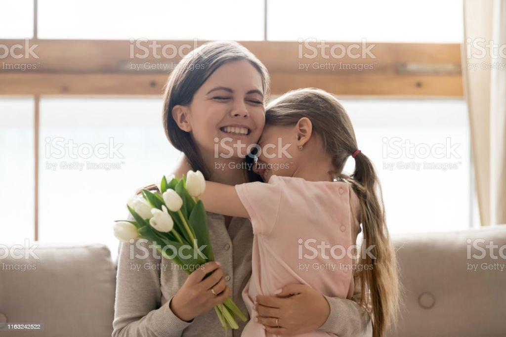 Loving cute preschooler girl hug mom congratulating her with birthday...