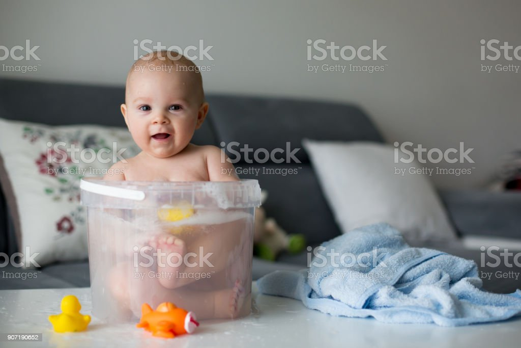 Cute little four month old baby boy, playing in bucket full with water stock photo