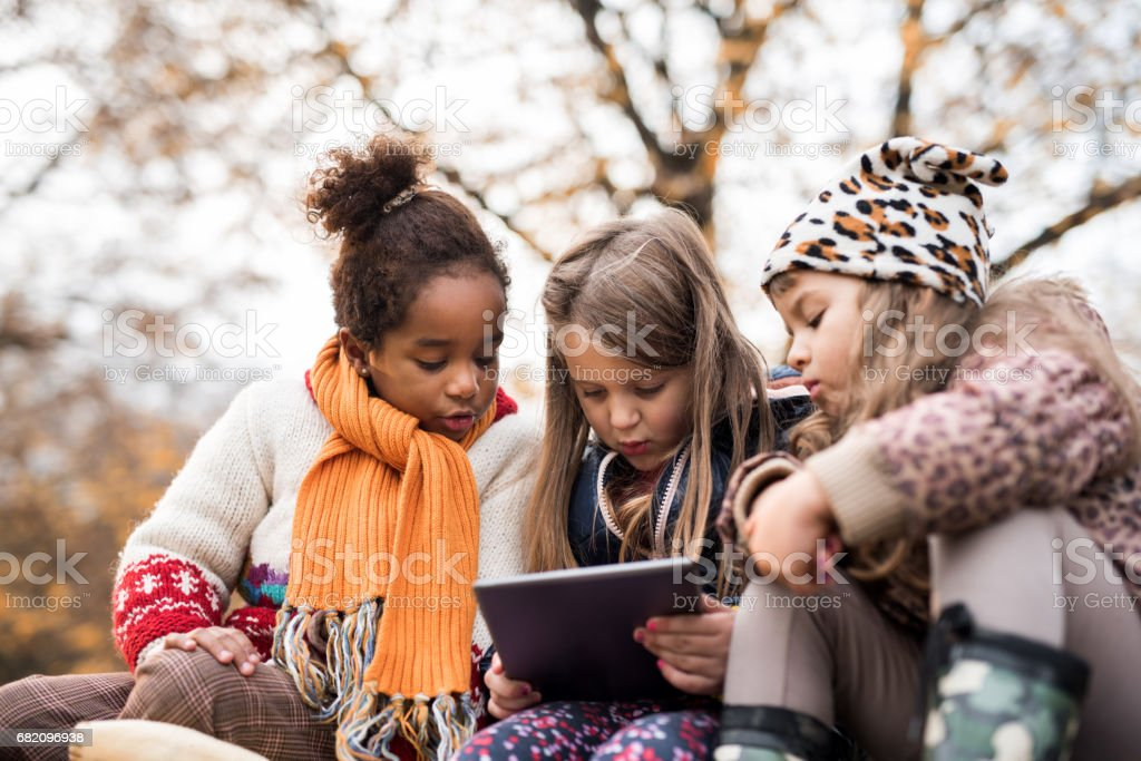 Cute little friends using digital tablet in nature. stock photo