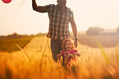 Cute little girl with her father holding balloons and running through field