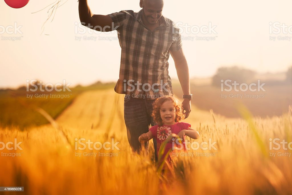 Cute little girl and father with balloons at field stock photo