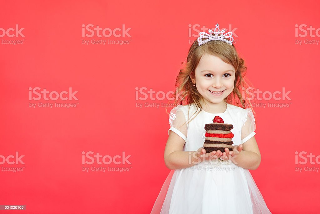 cute little girl and her birthday cake on red background stock photo