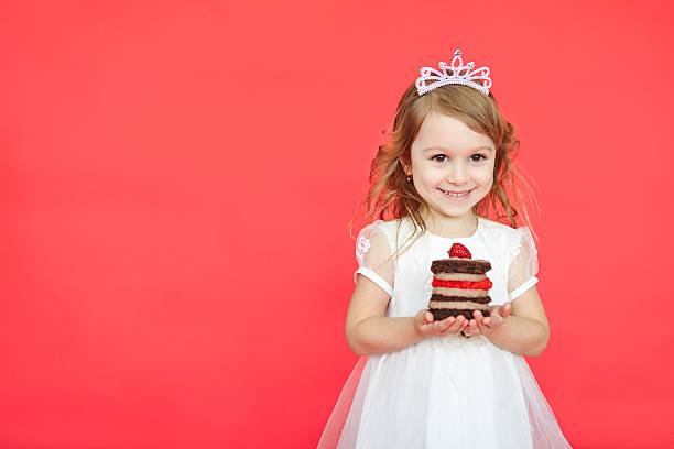 niedlich kleines mädchen und ihr geburtstagstorte auf rotem hintergrund - prinzessinnen torte stock-fotos und bilder