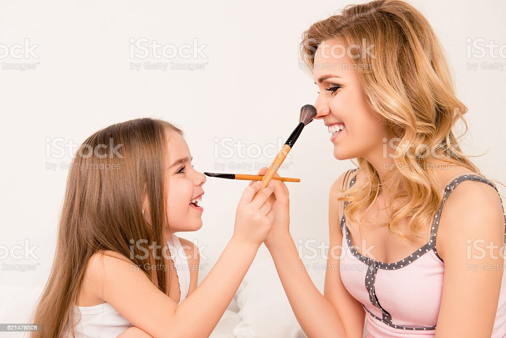 cute little girl and her mom doing each other maquillage stock photo