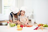 Cute little girl and her mom in chef's hats are cutting vegetables cooking a salad and smiling