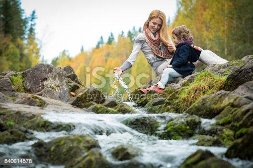 istock Cute little girl and mother in autumn forest 840614578
