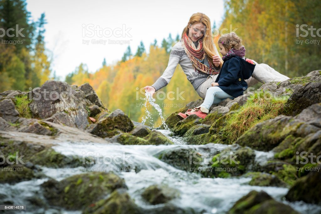 Cute little girl and mother in autumn forest stock photo
