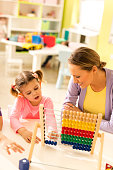 High angle view of smiling teacher and little girl using abacus at preschool.