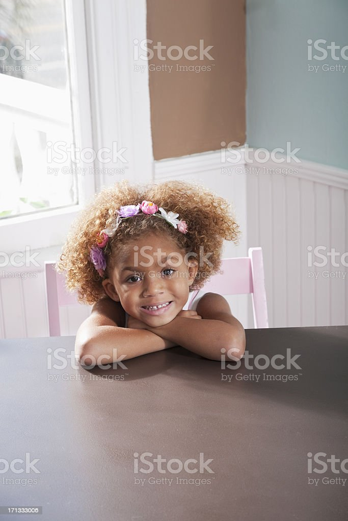 Cute little girl at table smiling stock photo