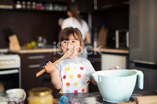 istock Cute little girl baking at home with mom 1142652471