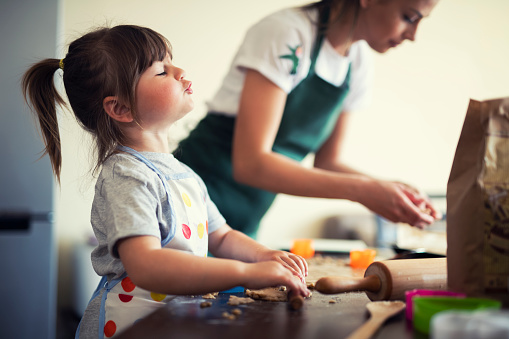 Cute little girl baking at home with mom, young mother and daughter making cookies in the kitchen.