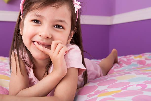 niedliche kleine mädchen portrait mit einem schlafzimmer - lila mädchen zimmer stock-fotos und bilder