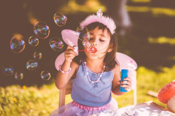 niedliche kleine mädchen bläst seifenblasen auf garten frühjahr tee party - kinder picknick spiele stock-fotos und bilder