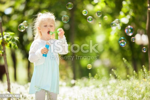 507271044istockphoto Cute little girl blowing bubbles in the park 178063056