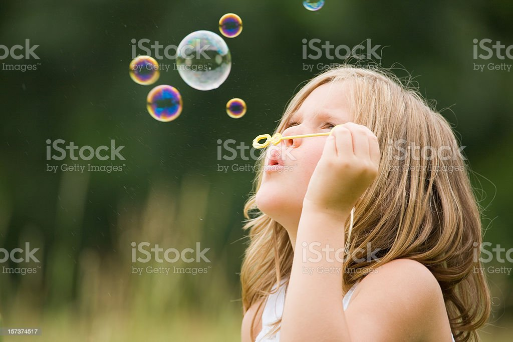 Cute little girl blowing bubbles outdoors royalty-free stock photo