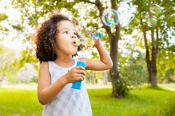Cute Little Girl Blowing Bubbles stock photo