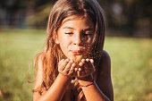 Cute little girl blowing gold glitter in a park
