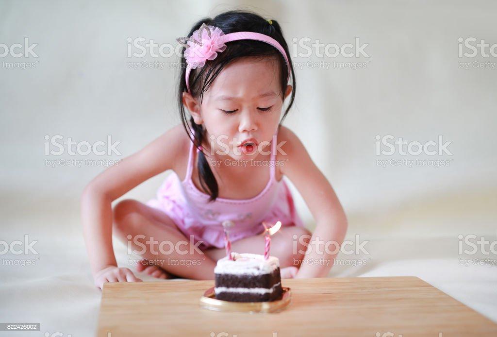 58436048b0 Niña linda que sopla velas de cumpleaños pequeño, niño de 2 años  celebrando. foto
