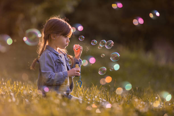 Cute little girl blowing soap bubbles in the park. stock photo