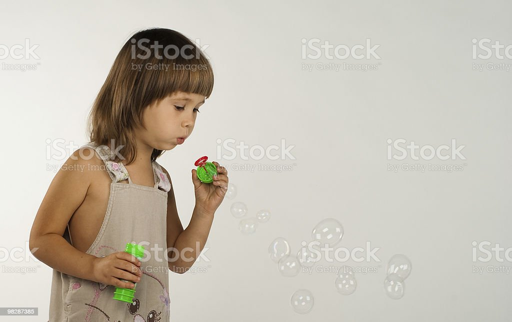 Cute little girl blowing soap bubbles royalty-free stock photo