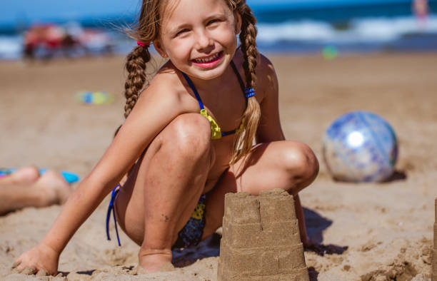 cute little girl building sandcastle on the sandy beach - girl alone in swimsuit stock photos and pictures