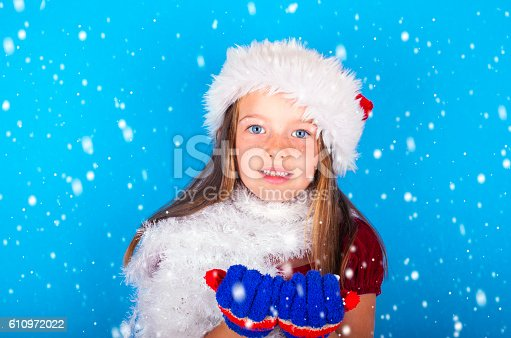 istock Cute little girl catching snow flakes 610972022