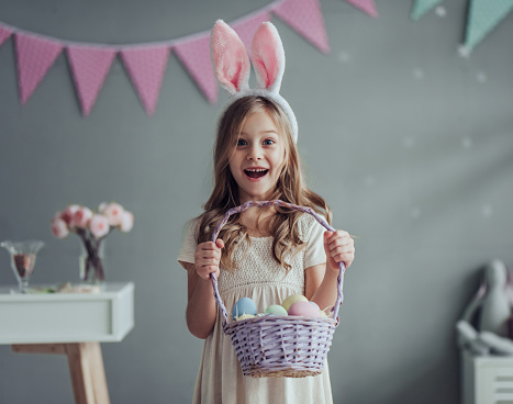 Little cute girl with bunny ears is standing with basket full of colorful Easter eggs while preparing for Easter celebration.