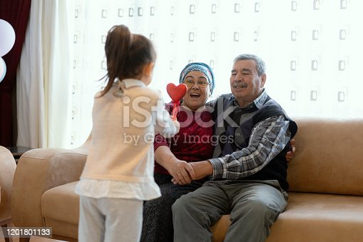 Cute little girl celebrating Valentine's day with grandparents, family and herself, holding heart shape decorations, home interior.