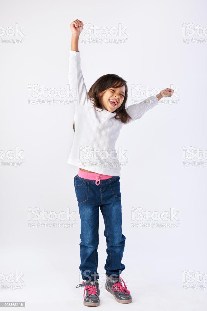 Niedliche kleine Mädchen feiern mit Armen oben in der Luft – Foto