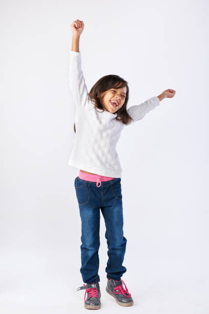 cute little girl celebrating with arms up in the air - african youth jumping for joy stock photos and pictures