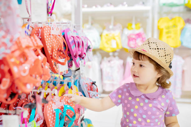 Cute little girl choosing clothes in the shop stock photo