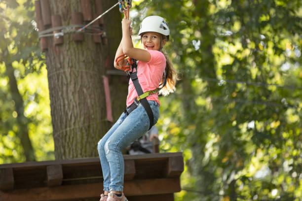 Cute little girl climbing in adventure park stock photo
