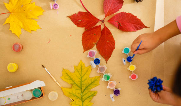 Cute little girl coloring a natural cone fir to create a flower, set of brushes, paints, natural autumn materials, create fun and easy with children, diy for kindergarten stock photo