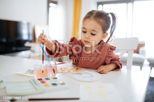 Beauty small girl sitting at the table, holding painting brush and drawing
