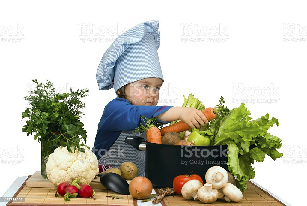 Cute little girl cooking soup with lots of different vegetables royalty-free stock photo