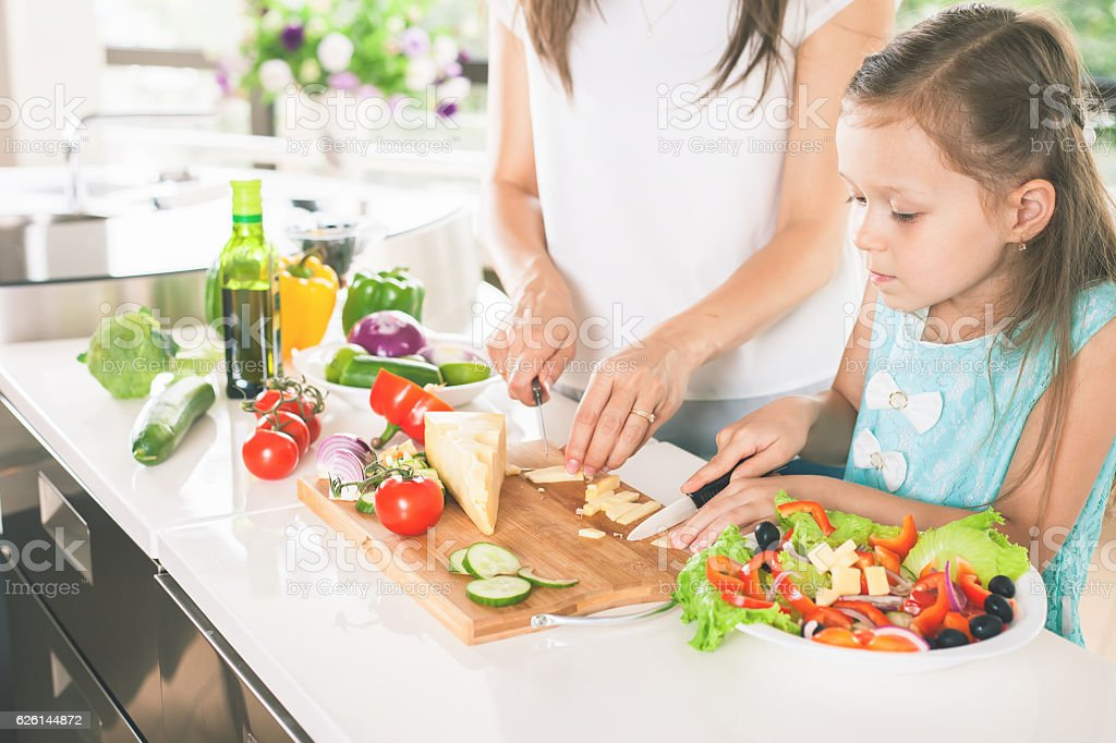Cute little girl cooking with her mother, healthy food stock photo