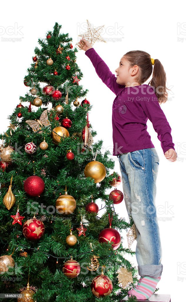 Cute Little girl decorates a Christmas tree royalty-free stock photo