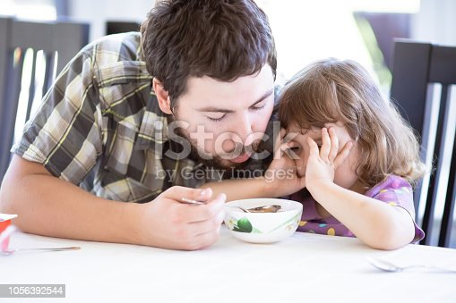 istock Cute little girl doesnt want to eat. Kid refusing food. Sad child 1056392544