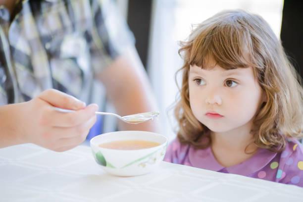 cute little girl doesn't want to eat. kid refusing food. sad child - desperdício alimentar imagens e fotografias de stock